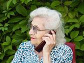 Mogen kvinna talar i en mobiltelefon — Stockfoto