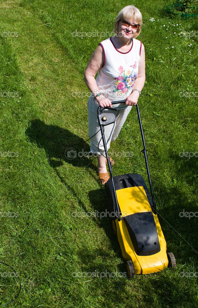 A woman with an electric mower at the cottage  Stock Photo #3844326