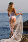 Young bride stands on a rock near the sea — Stock Photo