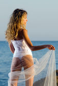 Young bride stands on a rock — Stock Photo