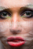 The woman's face with bright makeup veiled with gauze — Stock Photo