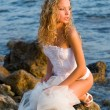 Stock Photo: Young bride sitting on rock