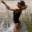 Young woman splashing in the water - Stockfoto