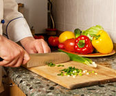 Cook chopped onion on a wooden board — Stock Photo