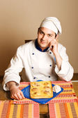 Handsome young chef in the living room w — Stok fotoğraf