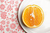 Orange on plate on napkin — Stock Photo