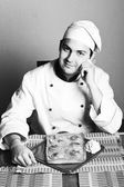 Handsome young chef in the living room w — Stock Photo