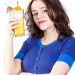 Beauty woman in blue dress with yellow orange juice — Stock Photo