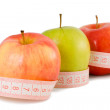 Pink measuring tape and three apples - Stock Photo