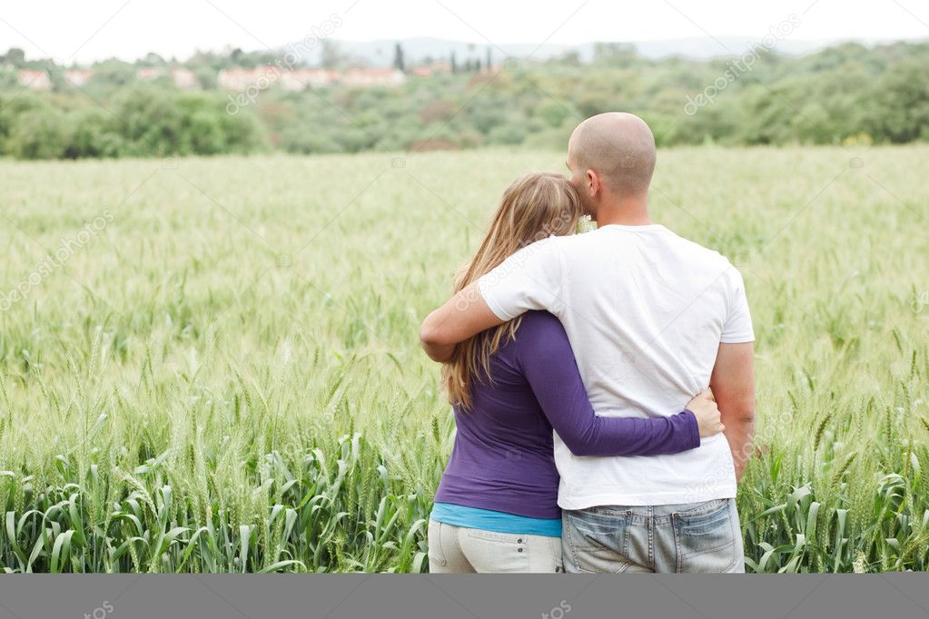 Rear view of couple with arms around each other in the park  Stock Photo #2890998
