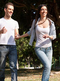 Young couple running in the park — Stock Photo