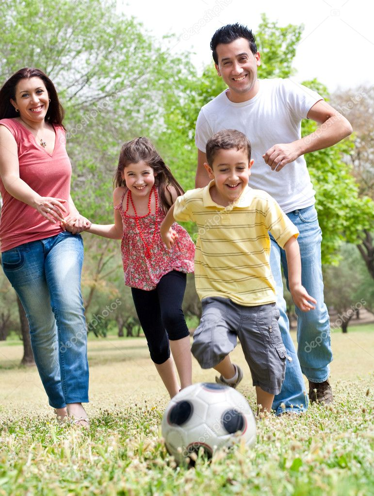 Happy family run to the soccer ball in the park, outdoor — Stock Photo #3040759