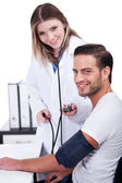 Female doctor checking blood pressure — Stock Photo