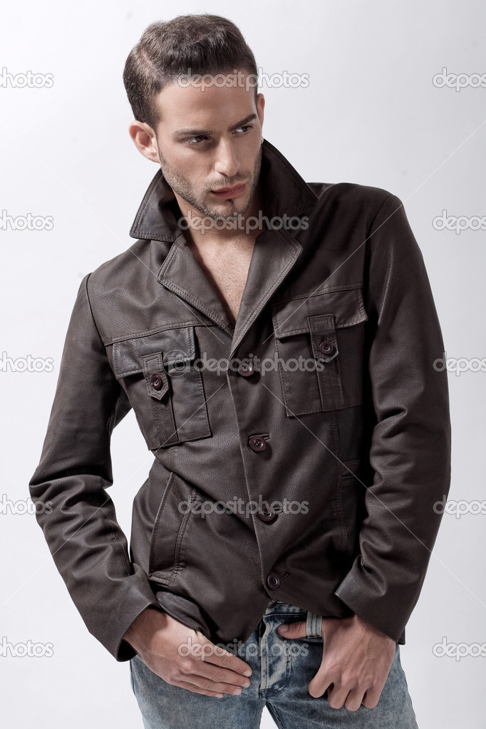 Young male model with brown jacket over grey background — Stock Photo #3055136