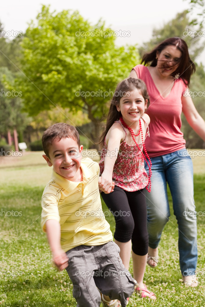 Family of three running in the park son on the front — Stock Photo #3114923