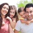 Couple with two young children piggyback — Stock Photo