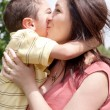 Children kissing his mom in the park — Stock Photo