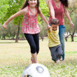 Childrens playing soccer with mother — Stock Photo