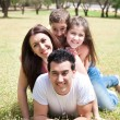 Happy family lying in the grass field — Stockfoto