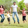 Family jumping together in the park — ストック写真