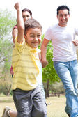 Young boy embrassing in park with family — Stock Photo