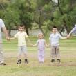 Happy family holding hands — Stock Photo