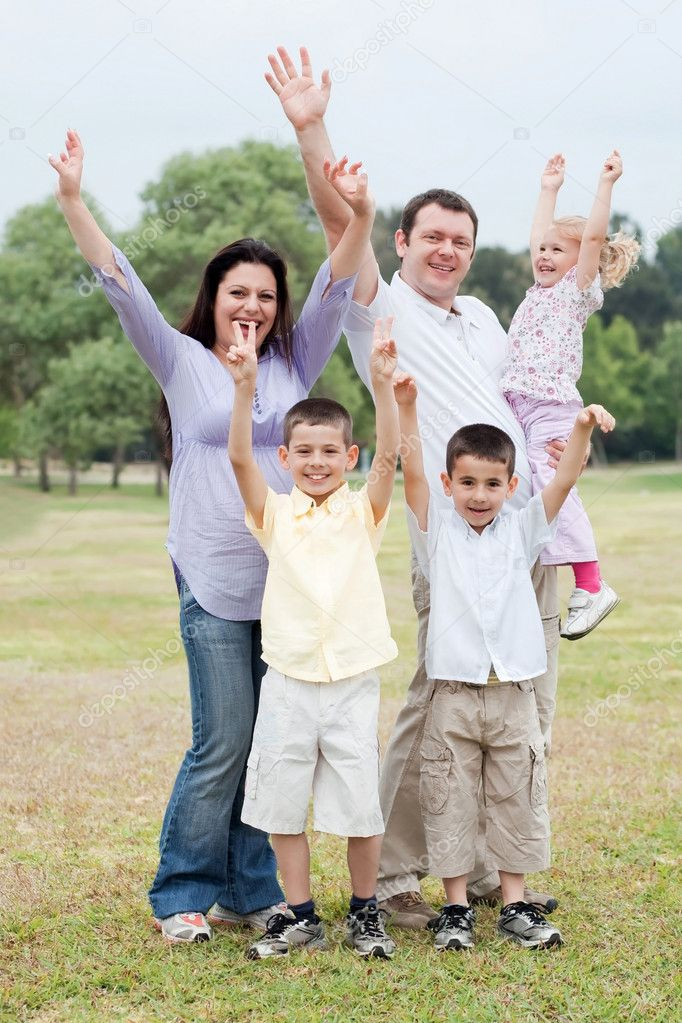 Happy family enjoying by raising hands on natural background and looking at you — Stock Photo #3136402