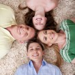Happy family lying  with their heads — Stockfoto