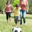Family playing soccer and having fun - Stock Photo