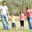 Family posing to camera in the park — Stockfoto