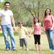 Family posing to camera in the park — Stock Photo #3308976