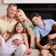 Happy domestic family sitting in living room with dog — Stock Photo