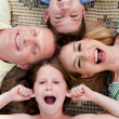 Stock Photo: Happy family of four lying on the carpet with their heads together