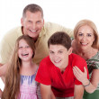 Happy family smiling towards the camera - Stockfoto