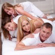 Cheerful family having fun together lying on a bed — Stock Photo #3309255