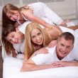 Cheerful family having fun together lying on a bed — Stock Photo