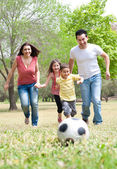 Parents and two young children playing soccer in the green field — Stock Photo