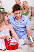 Surprised young kids with gift boxes sitting in the living room — Stock Photo