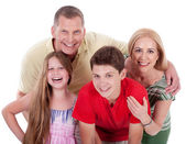 Happy family smiling towards the camera — Stock Photo