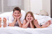Loving Brother and sister lying and having fun on the bed — Stock Photo