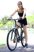 Young fitness woman on bicycle — Stock Photo