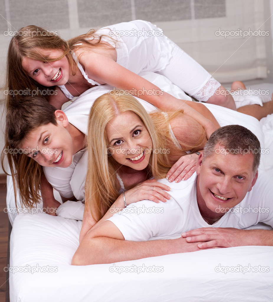 Cheerful family having fun together lying on a bed in living room  — Stock Photo #3309255