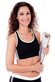 Fitness woman holding a blank clip board — Stock Photo
