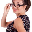 Young pretty woman in side pose looking at you over her glasses — Stock Photo