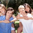 Two young men giving her lover piggy back in park — Stockfoto