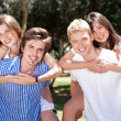 Two young men giving her lover piggy back in park — Stock Photo #3436076