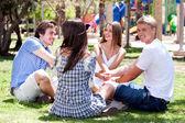 Sorrindo jovens casais sentados juntos, joga o jogo e se divertindo — Fotografia Stock