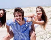 Young men giving piggy back to his women — Stock Photo