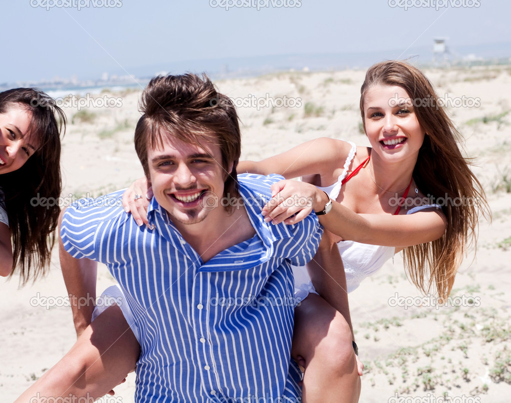 Young men giving piggy back to his women and having fun on beach  over natural sea background — Stock Photo #3436112