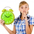 Foto Stock: Girl with clock asking us to maintain silence